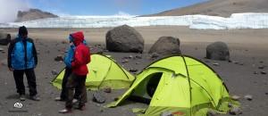 Kilimandscharo, Zelte stehen auf dem Krater, Gletscher im Hintergrund.